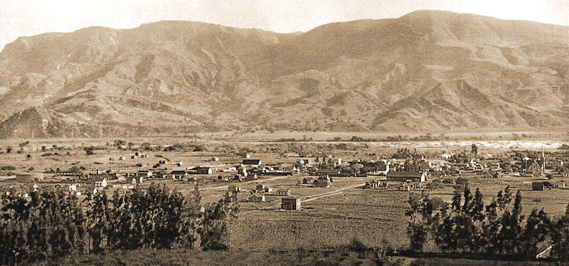A few scattered homes, farms, and commercial buildings in Santa Paula in 1888. Santa Clara River flows along mountains  south of the city.